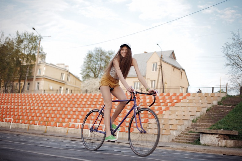 自転車に乗って通過する白い帽子を被った若い女性